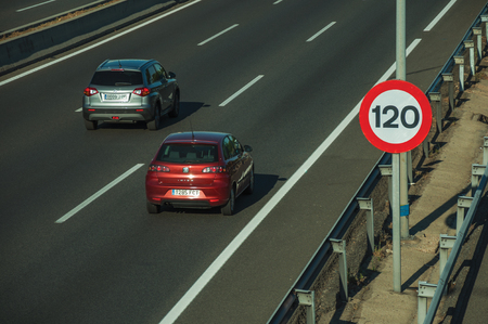 Madrid, Spain - July 25, 2018. Cars passing through highway and SPEED LIMIT signpost, on sunset in Madrid. Capital of Spain this charming metropolis has vibrant and intense cultural life. Sajtókép
