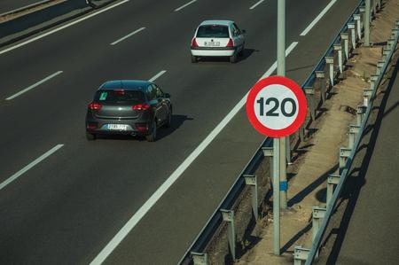 Auto che passano attraverso l'autostrada a più corsie e il cartello LIMITE DI VELOCITÀ, al tramonto a Madrid. Capitale della Spagna, questa affascinante metropoli ha una vita culturale vivace e intensa.