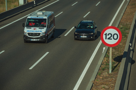 Madrid, Spain - July 25, 2018. Car and ambulance passing through highway and SPEED LIMIT signpost in Madrid. Capital of Spain this charming metropolis has vibrant and intense cultural life.