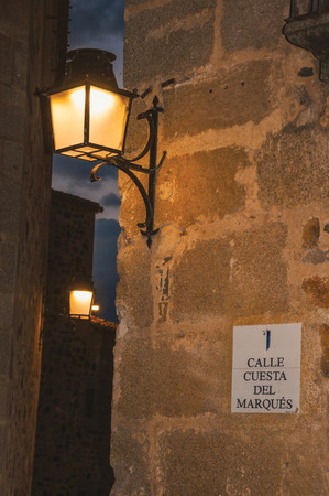 Old style metal sconce stuck to the stone wall and soft light in an alley at dusk in Caceres. A cute and charming town with a fully preserved medieval city center in western Spain. 写真素材