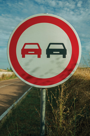 Close-up of NO OVERTAKING traffic sign on sunset, next a countryside road near Elvas. A gracious star-shaped fortress city on the easternmost frontier of Portugal. Retouched photo.