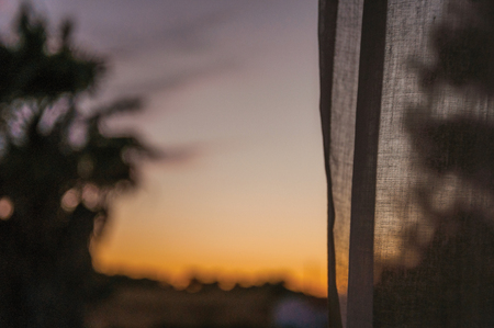 Countryside landscape with multicolored sky at sunset dusk and a curtain on the foreground in a farmstead near Elvas. A gracious star-shaped fortress city on the easternmost frontier of Portugal.
