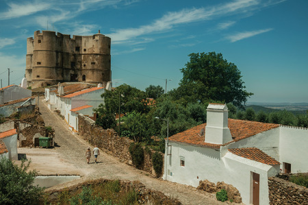 People walking up the main cobblestone street in a sunny day towards the Castle of Evoramonte. A tiny fortified civil parish over hill where stands out its historic castle in Portugal. Editorial