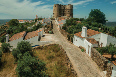 Landscape of empty main cobblestone street in a sunny day and the Castle on background at Evoramonte. A tiny fortified civil parish over hill where stands out its historic castle in Portugal. Banque d'images - 121871789