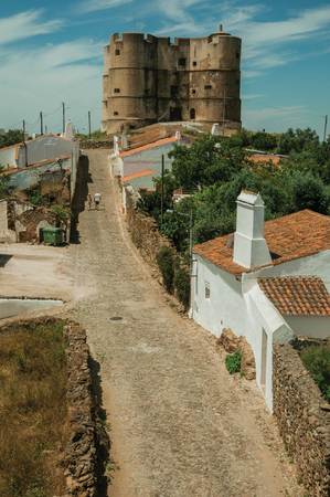 People walking up the main cobblestone street in a sunny day towards the Castle of Evoramonte. A tiny fortified civil parish over hill where stands out its historic castle in Portugal. Banque d'images - 121871792
