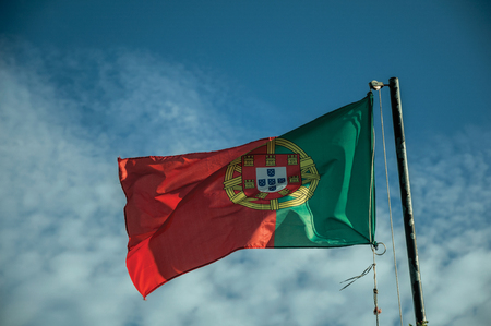 Close-up of Portuguese flag at sunset fluttering in the wind with blue sky on the background near Elvas. A gracious star-shaped fortress city on the easternmost frontier of Portugal.