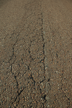 Close-up of cracked asphalt with small gravel inserted in it, on a countryside road at sunset near Elvas. A gracious star-shaped fortress city on the easternmost frontier of Portugal.
