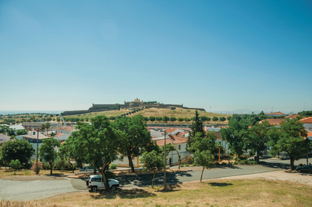 Street landscape with white houses and the de Santa Luzia Fort over a hill in the background, on a sunny day near Elvas. A gracious star-shaped fortress city on the easternmost frontier of Portugal. Stok Fotoğraf