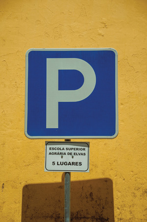 Yellow plaster wall behind a PARKING SPOT road sign with 5 places reserved for the Agrarian Higher School of Elvas. A gracious star-shaped fortress city on the easternmost frontier of Portugal.
