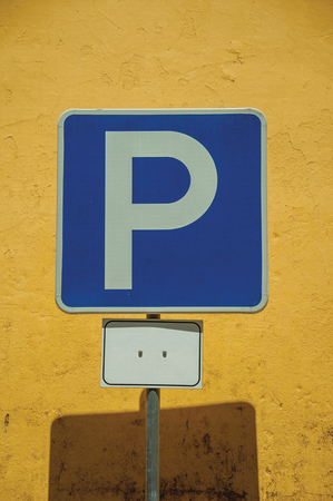Close-up of PARKING SPOT road sign in front of yellow plaster wall in a sunny day at Elvas. A gracious star-shaped fortress city on the easternmost frontier of Portugal. Retouched photo.