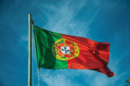 Close-up of Portuguese flag at sunset fluttering in the wind with blue sky in the background near Elvas. A gracious star-shaped fortress city on the easternmost frontier of Portugal. 版權商用圖片