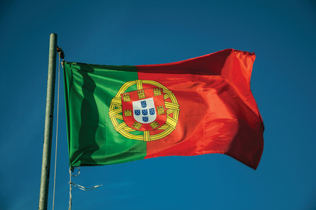 Close-up of Portuguese flag at sunset fluttering in the wind with blue sky in the background near Elvas. A gracious star-shaped fortress city on the easternmost frontier of Portugal. Banco de Imagens