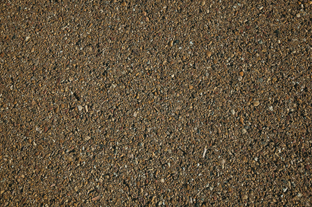 Close-up of asphalt with small gravel inserted in it, on a countryside road at sunset near Elvas. A gracious star-shaped fortress city on the easternmost frontier of Portugal.