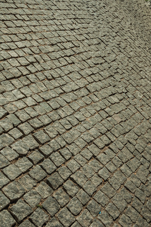 Close-up of pavement made of granite setts on alley in a sunny day, forming a singular background at Elvas. A gracious star-shaped fortress city on the easternmost frontier of Portugal. Banco de Imagens