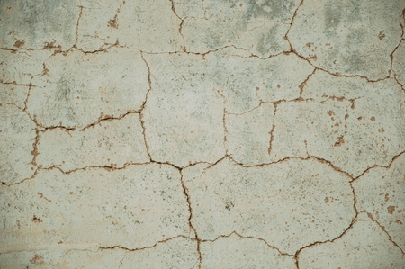 Close-up of wall covered by rough plaster with some cracks and chipped, forming a singular background at Portalegre. A nice little town at the bottom of Mamede Mountain Range in eastern Portugal.