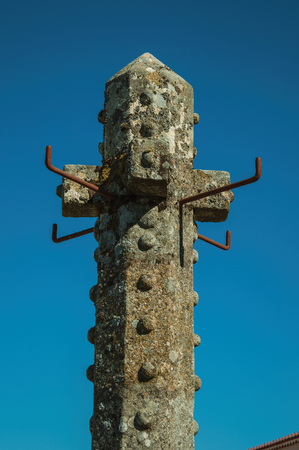 Top of tall carved stone pillory with blue sky in the background at Marvao. An amazing medieval fortified village perched on a granite crag in eastern Portugal.