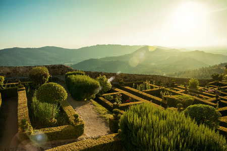 Leafy edge and bushes in a flowered garden on sundown, with mountainous landscape at Marvao. An amazing medieval fortified village perched on a granite crag in eastern Portugal. Retouched photo.