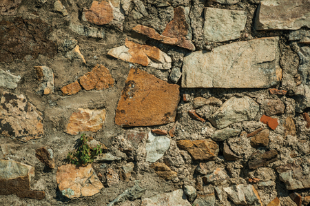 Close-up of old wall made of rough stones on sunny day, forming a singular background at the Marvao Castle. An amazing medieval fortified village perched on a granite crag in eastern Portugal. Banco de Imagens
