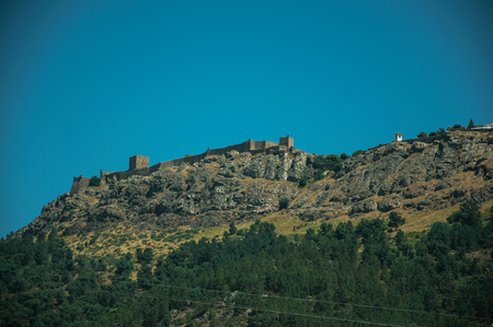 Marvao village on top of tall crag, with its stone walls, towers and white houses in a sunny day, seen from Portagem. A district of Marvão at the bottom of a lush wooded valley in eastern Portugal.