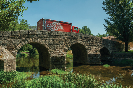 Marvao, Portugal - July 09, 2018. Beer truck passing over the old Roman stone bridge on the Sever River at Portagem. A district of Marvão at the bottom of a wooded valley in eastern Portugal.