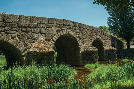 Old Roman stone bridge still in use over the Sever River with green plants on the bank, in a sunny day at Portagem. A district of Marvão at the bottom of a lush wooded valley in eastern Portugal.