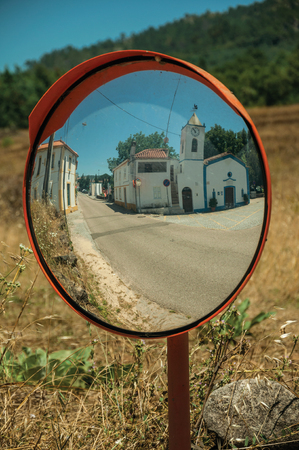 Little church and white house reflected in street mirror, in a sunny day in the small countryside village of Portagem. A district of Marvão at the bottom of a lush wooded valley in eastern Portugal.