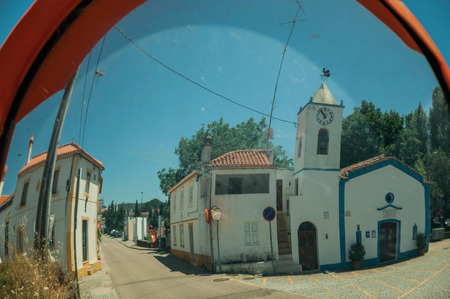 Little church and white house reflected in street mirror, in a sunny day in the small countryside village of Portagem. A district of Marvão at the bottom of a lush wooded valley in eastern Portugal. 版權商用圖片
