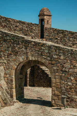 Arched gateway in the city outer wall made of stone with pathway under it and watchtower, on sunny day at Marvao. An amazing medieval fortified village perched on a granite crag in eastern Portugal. Archivio Fotografico