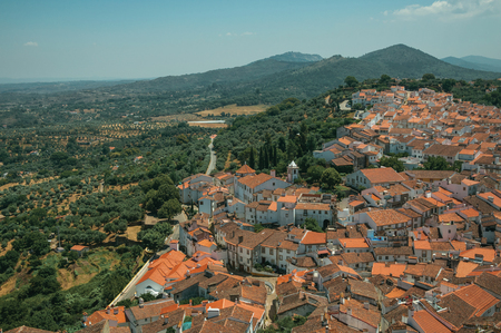 City landscape with old building roofs, church steeple and green hills, in a sunny day at Castelo de Vide. Nice little town with medieval castle to ensure the defense of the Portugal eastern border.