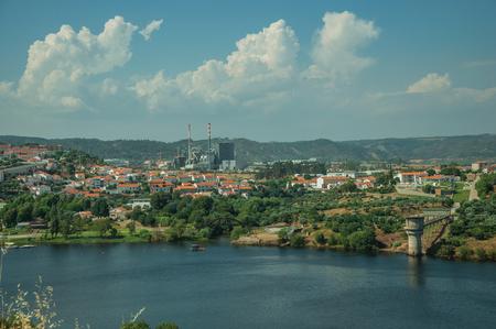 Breiter Fluss Tejo entlang hölzerner Hügel mit Zellstoff- und Papierindustrie am Horizont, in der Nähe von Castelo Branco. Freundliche und wichtige Stadt, es war ein ehemaliges Bistum in der zentralen Region Portugals. Standard-Bild