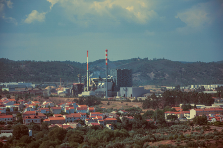 Close-up of pulp and paper industrial plant on horizon next to houses, near Castelo Branco. Friendly and important city, it was a former bishopric in the central region of Portugal. Vintage filter. Imagens