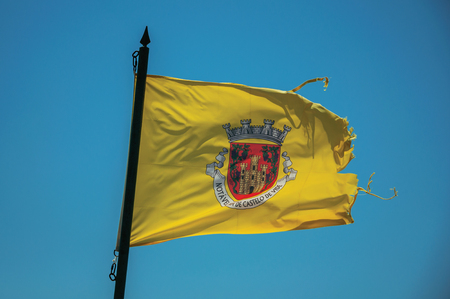 Flag with the coat of arms of the city fluttering in the wind on the castle wall at Castelo de Vide. Nice little town with medieval castle to ensure the defense of the Portugal eastern border.