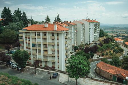 Stadtbild mit Mehrfamilienhaus inmitten von Bäumen und hügeliger Landschaft, an einem bewölkten Tag bei Covilha. Bekannt als die Stadt der Wolle und des Schnees, liegt in der Nähe des Estrela-Kamms im Osten Portugals.