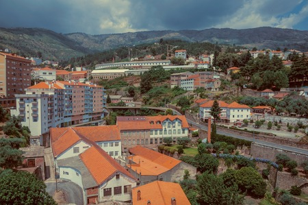 Cityscape with road and building amid trees and hilly landscape, in a cloudy day at Covilha. Known as the town of wool and snow, stands at Estrela ridge proximity in eastern Portugal. Vintage filter. 写真素材