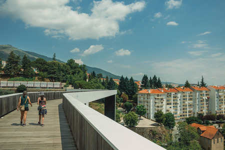 Covilha, Portugal - July 11, 2018. Woman and child walking on footbridge over valley with building at Covilha. Known as the town of wool and snow, stands at Estrela ridge proximity in eastern Portugal Editorial