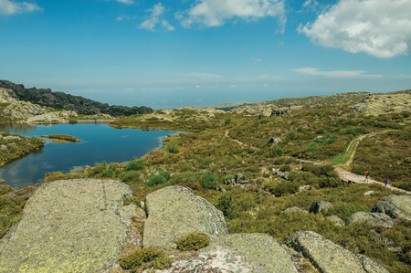 Dam lake at the Covao dos Conchos among rocky terrain and trails on highlands, in a sunny day at the Serra da Estrela. The highest mountain range in continental Portugal, with astonishing scenery. Stockfoto