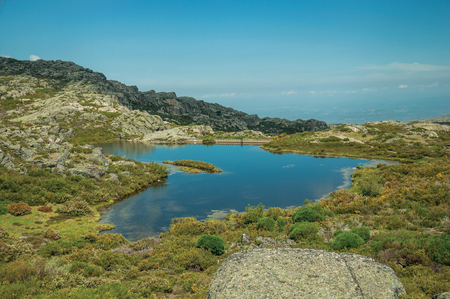 Dam lake at the Covao dos Conchos among rocky terrain and bushes on highlands, in a sunny day at the Serra da Estrela. The highest mountain range in continental Portugal, with astonishing scenery.