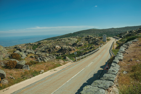 Long roadway going through rocky landscape on highlands covered by green bushes, in a sunny day at the Serra da Estrela. The highest mountain range in continental Portugal, with astonishing scenery. Фото со стока