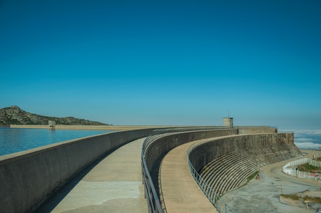 Pathway over the Marques da Silva concrete dam forming the Long Lake on highlands, in a sunny day at the Serra da Estrela. The highest mountain range in continental Portugal, with astonishing scenery.