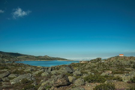 Rocky landscape covered by bushes with the Long Lake and house on highlands, in a sunny day at the Serra da Estrela. The highest mountain range in continental Portugal, with astonishing scenery. 写真素材