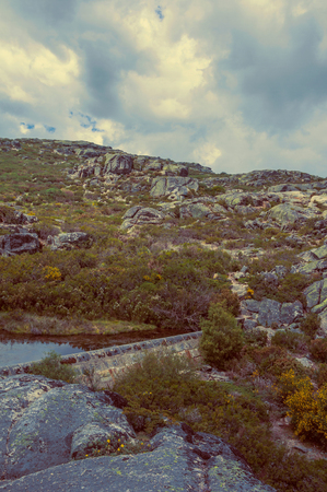 Hilly landscape at the Covao dos Conchos dam lake on the rocky highlands of the Serra da Estrela. The highest mountain range in continental Portugal, with astonishing scenery. Vintage filter.