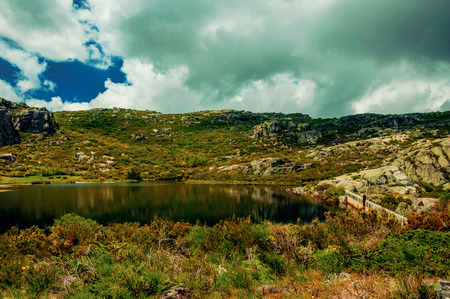 Dam lake at Covao dos Conchos among rocks and bushes on highlands, in a sunny day at the Serra da Estrela. The highest mountain range in continental Portugal, with astonishing scenery. Retouched photo Stockfoto