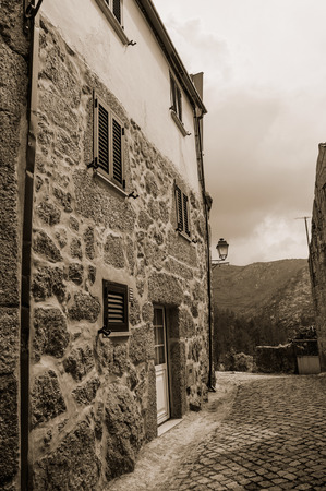 Facade of old house with stone wall in a deserted alley at Sabugueiro. A village in the middle of the Serra da Estrela, an amazing mountain range in eastern Portugal. Black and white photo. 免版税图像