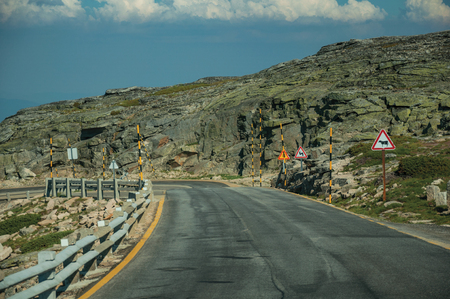 Roadway crossing hilly landscape covered by rocks and bushes in a sunny day, at the highlands of the Serra da Estrela. The highest mountain range in continental Portugal, with astonishing scenery.