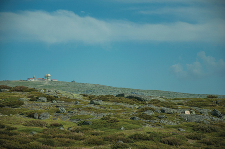 Hilly landscape covered by bushes and rocks with domes of an old radar station on the highlands at the Serra da Estrela. The highest mountain range in continental Portugal, with astonishing scenery.