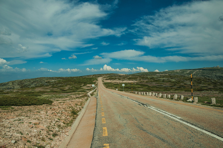 Long roadway passing through rocky landscape and bush fields in a sunny day, at the highlands of the Serra da Estrela. The highest mountain range in continental Portugal, with astonishing scenery.