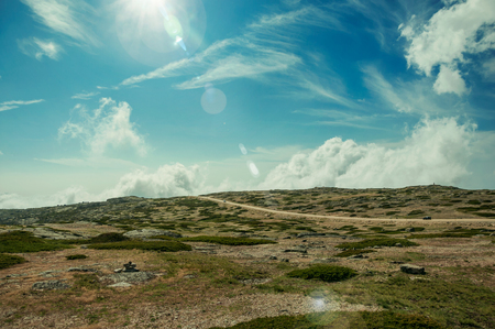 Road with cars passing through rocky landscape on sunny day, at the highlands of the Serra da Estrela. The highest mountain range in continental Portugal, with astonishing scenery. Retouched photo.