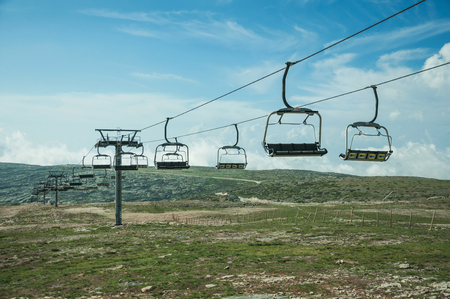Chairlift towers and cables over hilly landscape covered by bushes and rocks, on the highlands at the Serra da Estrela. The highest mountain range in continental Portugal, with astonishing scenery.