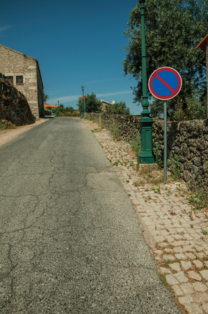 Asphalt road on slope with light post and NO PARKING traffic sign on the cobblestone sidewalk, in a sunny day at Monsanto. Considered one of the cutest and most peculiar historic village of Portugal. Stock Photo