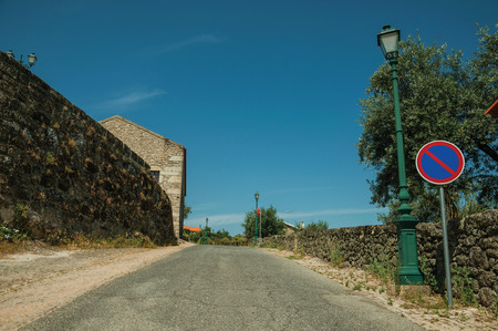Asphalt road on slope with light post and NO PARKING traffic sign on the cobblestone sidewalk, in a sunny day at Monsanto. Considered one of the cutest and most peculiar historic village of Portugal. Imagens